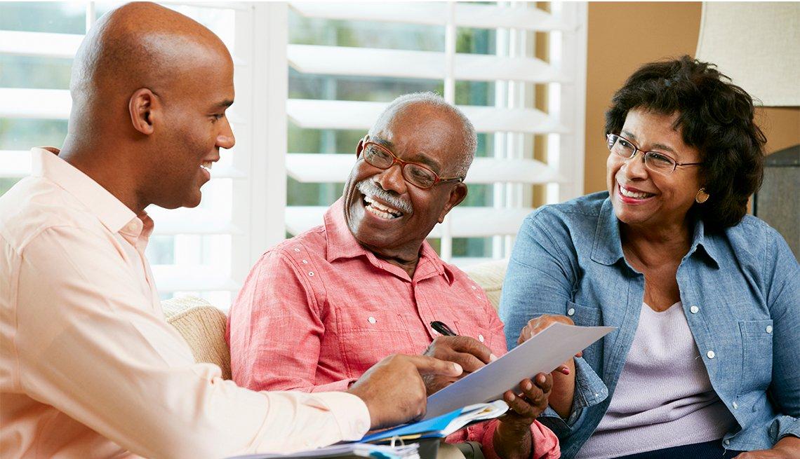 Asesor financiero con una pareja en la sala de su casa.