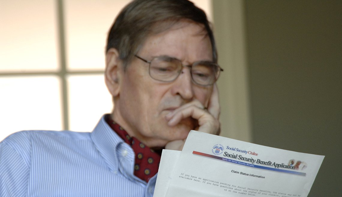 Senior man reading Social Securty Benefit paperwork