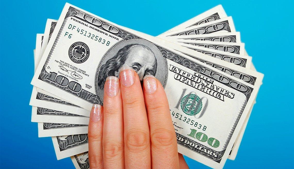 Mano de una mujer sosteniedo billetes de 100 dólares.
