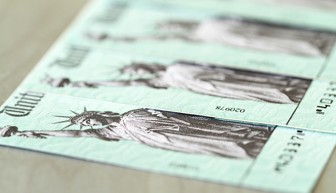 A line of US Treasury checks, like those used for  Social Security benefits, with selective focus on first check.