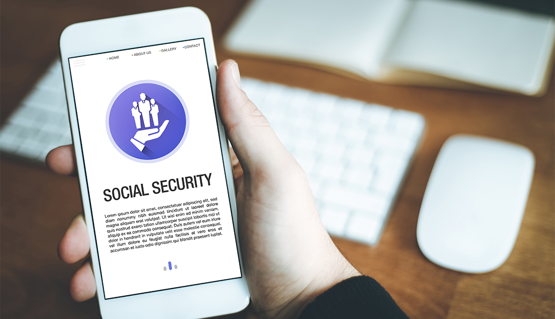 Social Security words displayed on a smartphone held in one hand over desk