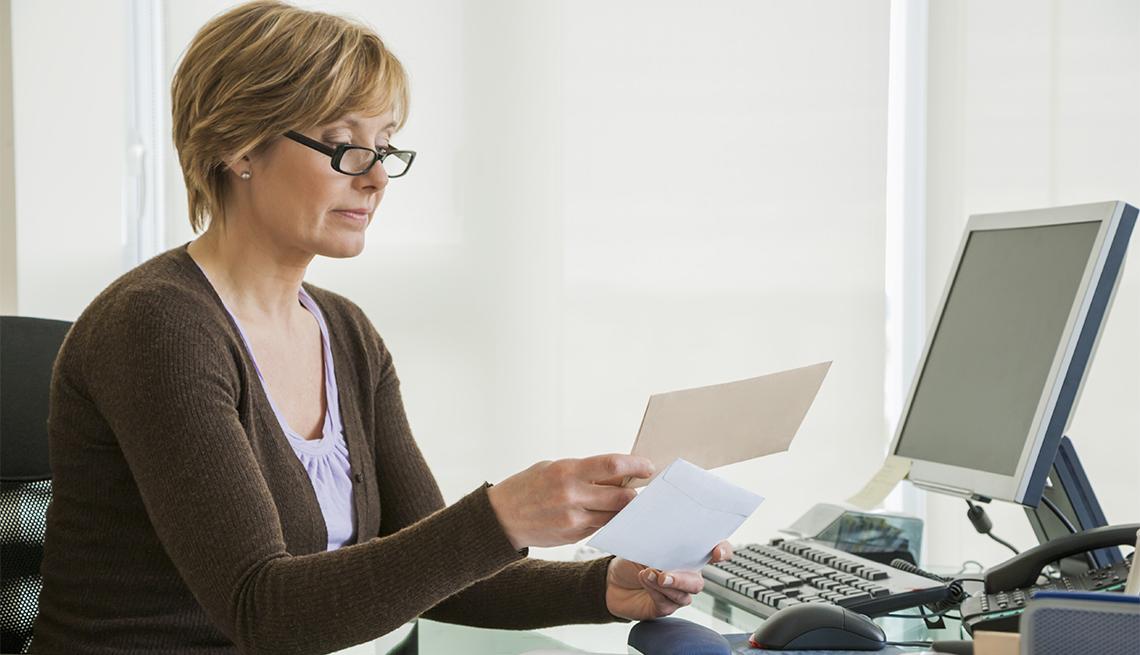 Woman looking at bills at computer