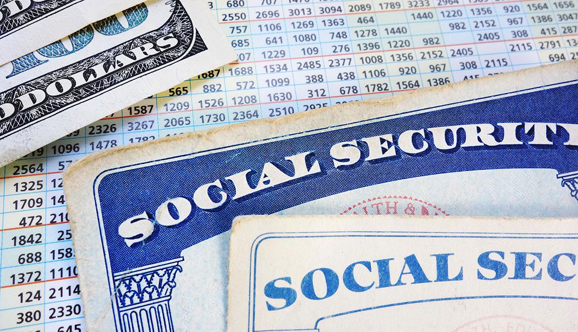 Tarjeta nueva y vieja del Seguro Social sobre un listado de cifras por año y billetes de 100 dólares