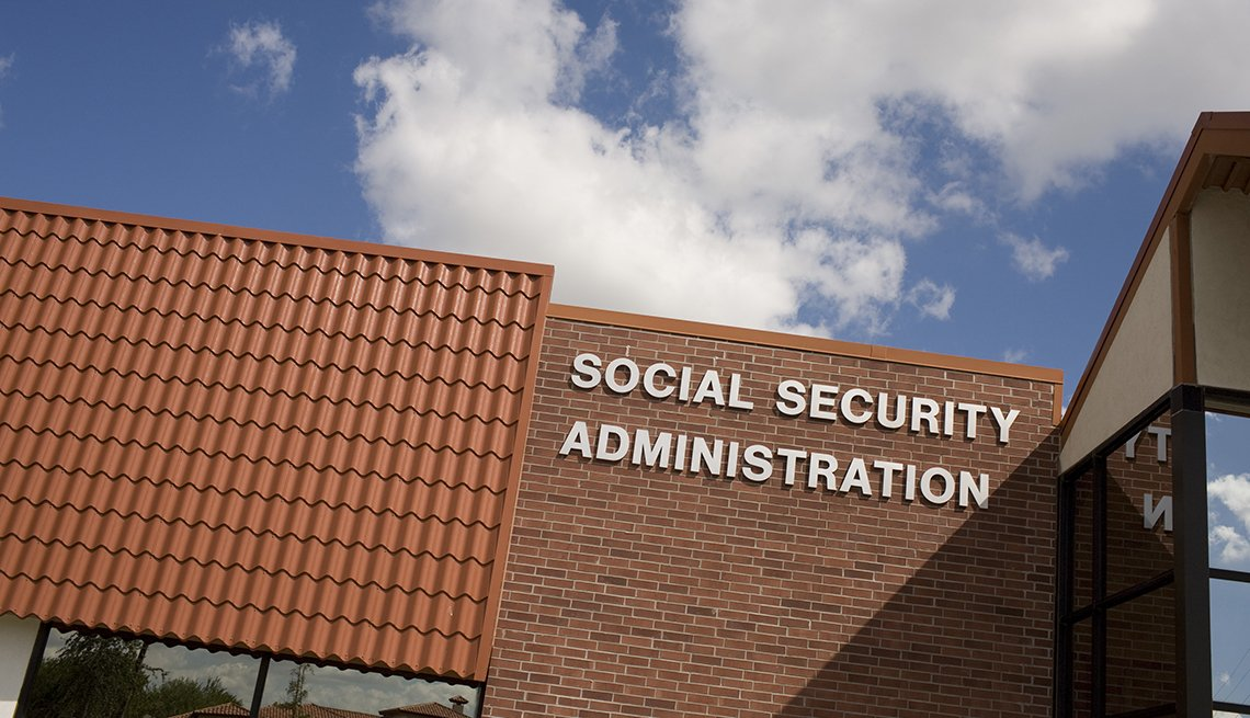 exterior red brick Social Security Administration office in Brownsville Texas against bright blue sky and white clouds