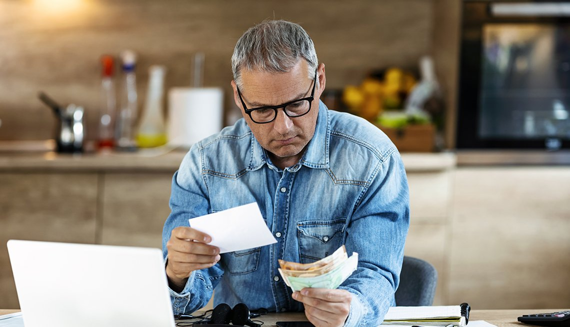 man wearing glasses with worried look on his face sits next to an open laptop computer and examines invoices and bills