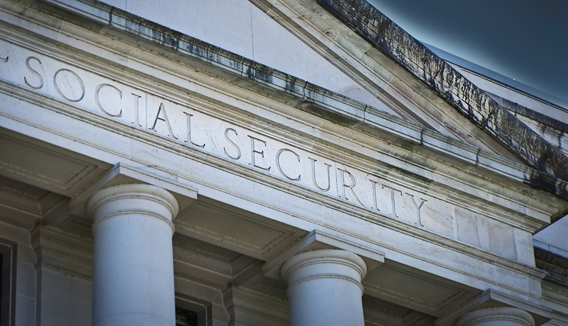 front of large marble greek architecture building with social security as the sign engraved on it