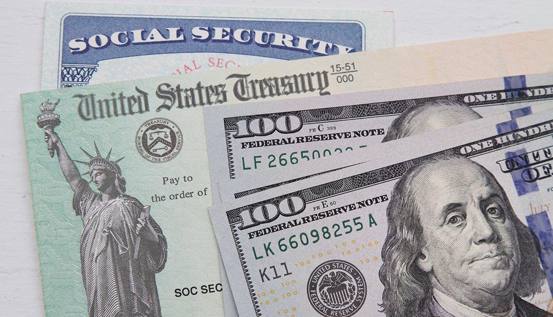 Tarjeta del Seguro Social, detrás de un cheque del Departamento del Tesoro de EE.UU. y dos billetes de $100 dólares.