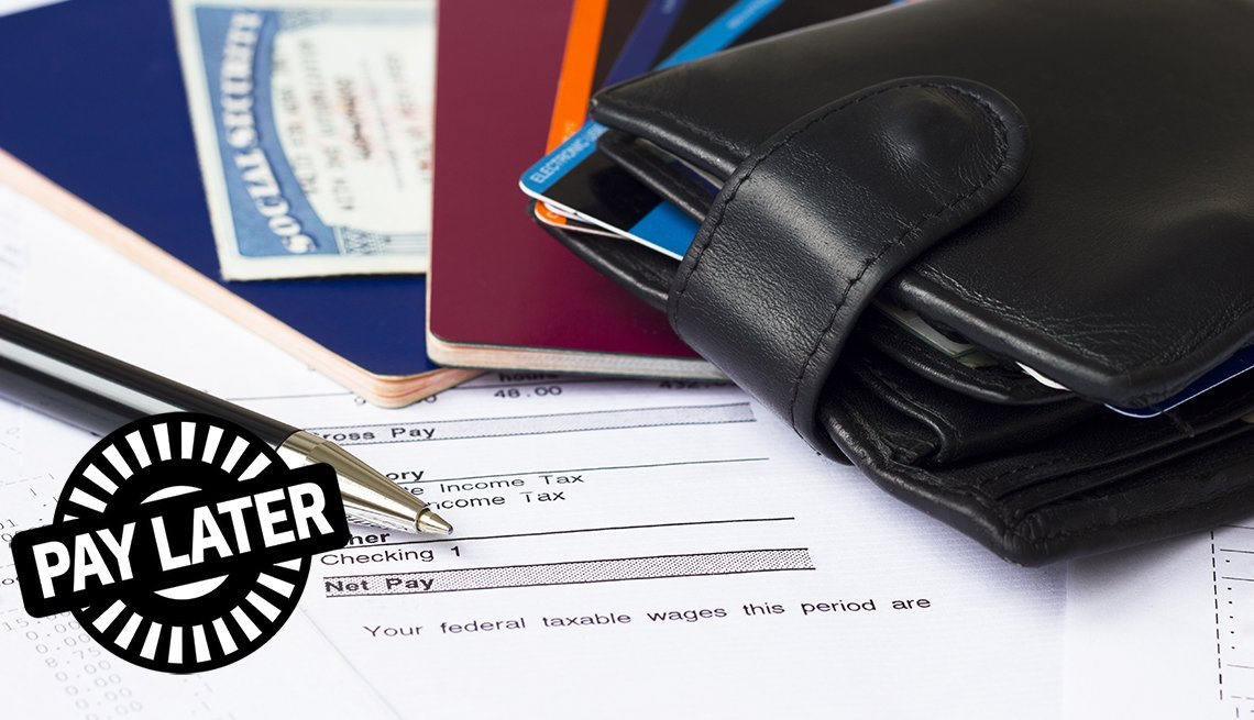 pay later stamp on top of paycheck, pay statements, wallet, passports, credit cards and social security card