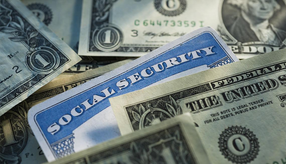 social security card displayed among dollar bills