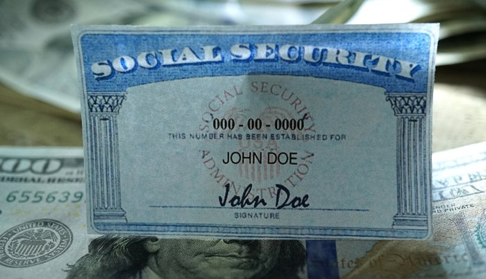 close up photo of a social security card over U.S. currency
