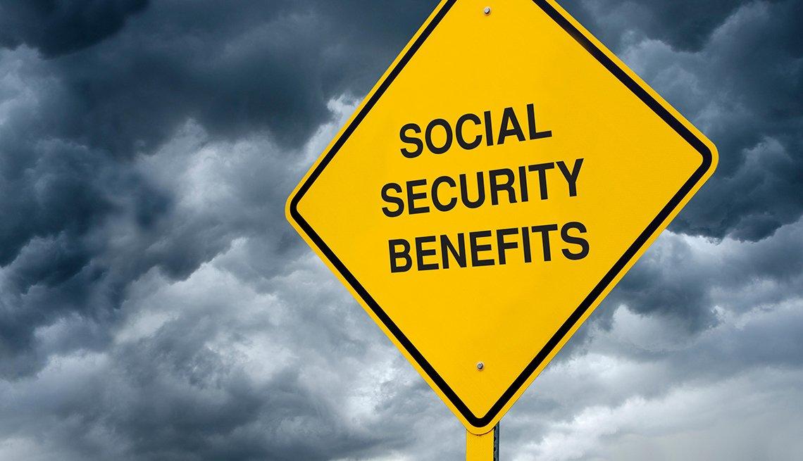 Señal de tránsito con un letrero en inglés que dice beneficios del Seguro Social.