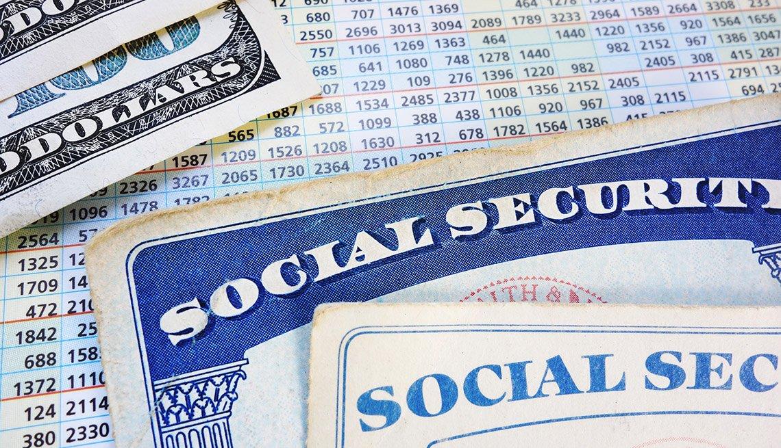 Tarjeta del Seguro Social y billetes de 100 dólares sobre una lista de números.
