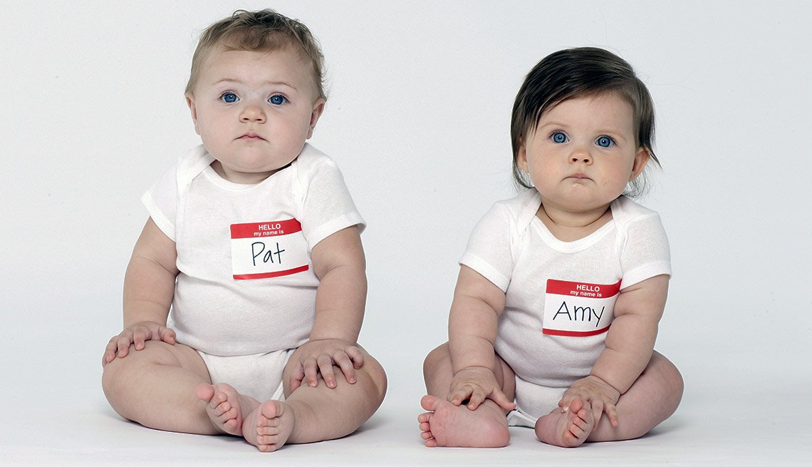 Two babies sit facing camera wearing stick on name tags on white tshirts that say Pat and Amy