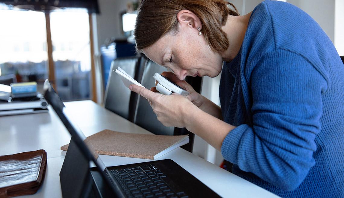 Mujer invidente sentada frente a una mesa donde lee un documento con una lupa
