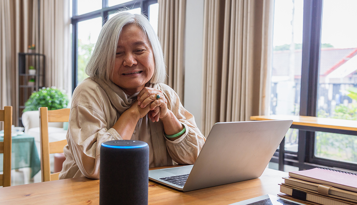 Woman at home listening to her voice assistant device