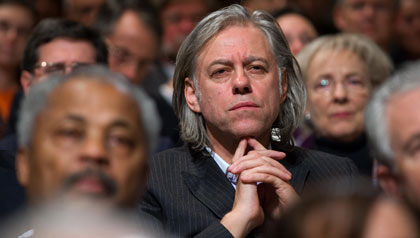 Activist Bob Geldof listens to President George W. Bush speak about international development