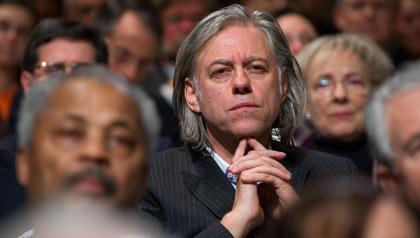 Activist Bob Geldof listens to President George W. Bush speak about international development
