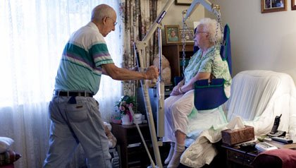 Carl Meyers, uses a Hoyer hoist to move his wife to a recliner.