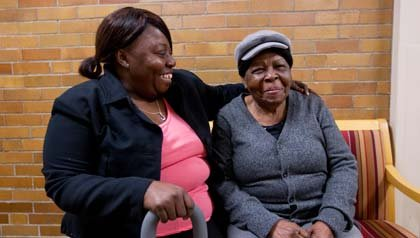 Paulette Martin, left, visits with her mother, Joyce Martin, at a program for people with dementia. AARP Massachusetts says those services should receive adequate funding.