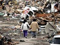 Las mujeres caminan por una calle cubierta de escombros del tsunami en Ofunato, prefectura de Iwate, Japón, el lunes, Marzo 21, 2011.