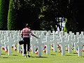 A women touches one of the crosses in the American Military Cemetery near Omaha Beach, Colleville sur Mer in Normandy, France