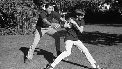 Gov. Ronald Reagan and son, Skipper, both football fans, play touch football in the backyard of their Sacramento home on Nov. 15, 1971.