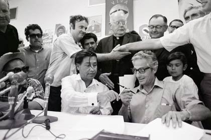 Hands of a grower and a farm worker clasp in the background, as César Chávez (l) of the United Farm Workers (UFW) union and John Giumarra Sr., representing 26 of California's largest table grape growers, exchange pens to sign a contract with the UFW on July 29, 1970, in Delano, California. Chávez's UFW has pushed a boycott on table grapes for the past five years. With this signing, the UFW now has contracts with 85 percent of the table grape growers.