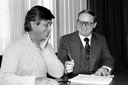 In 1978, Labor Secretary Ray Marshall, right, hands a pen to César Chávez, president of the United Farm Workers union, during a ceremony at which the DOL signed a $500,000 contract with Chávez to provide English language training and other services to approximately 1,500 migrant and seasonal farm workers.