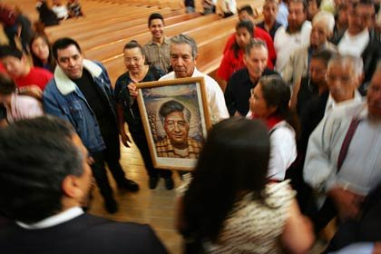 A man holds a portrait of César Chávez as Los Angeles mayoral run-off candidate Antonio Villaraigosa (l) and Christine Chávez (r), granddaughter of César, walk by in the Cathedral of Our Lady of the Angels on March 31, 2005 in Los Angeles, California. Hundreds of farm workers, labor union members, and civic and religious leaders attended the annual Mass honoring the late César E. Chávez, a life-long Catholic and founder of the United Farm Workers union.