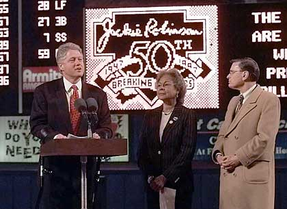 President Bill Clinton speaks at a ceremony for Jackie Robinson; next to him are Robinson's widow, Rachel Robinson, and MLB Acting Commissioner Bud Selig.