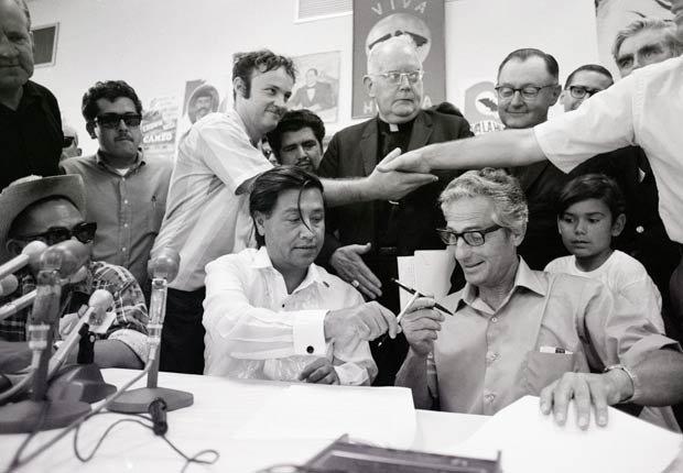 Un productor de uvas de mesa y un trabajador agrícola estrechan las manos, mientras César Chávez de la United Farm Workers (UFW) (izq.) y John Giumarra Sr., representando 26 de los más grandes productores de uva de California (der.), intercambian plumas para firmar un contrato en el que el UFW prestará sus servicios al 85% de los productores de uva de mesa en el estado, el 29 de julio de 1970, en Delano, California. El contrato viene después de cinco años de boicot al consumo de uvas alentado por la UFW.