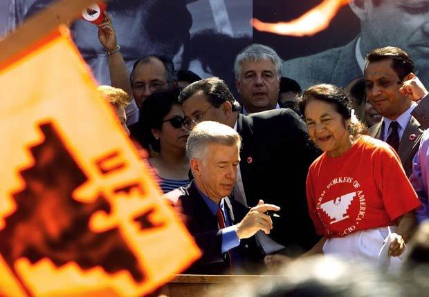 El gobernador de California Gray Davis, sentado en el centro, firma el 18 de agosto de 2000 la ley SB 984, que crea un nuevo día feriado en el estado de California en honor a César Chávez , el fundador del sindicato United Farm Workers. El autor de la ley, el Senador Richard G. Polanco, demócrata de Los Ángeles, se puede ver parcialmente detrás de Davis y a la derecha, la activista Dolores Huerta.
