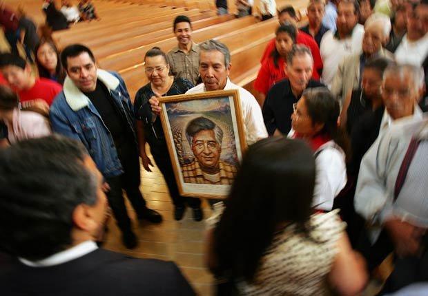 Un hombre sostiene un retrato de César Chávez, mientras el candidato a la alcaldía de Los Ángeles, Antonio Villaraigosa (izq.) y Christine Chávez (der.), nieta de César, caminan por la Catedral de Nuestra Señora de Los Ángeles el 31 de marzo de 2005. Cientos de trabajadores agrícolas, sindicalistas, y líderes cívicos y religiosos asistieron a la Misa anual en honor a César Chávez, fallecido en 1993.