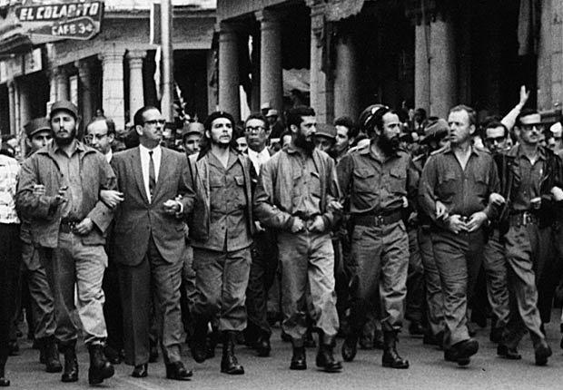 Fidel Castro y otros líderes cubanos caminando cogidos del brazo durante una procesión fúnebre por las víctimas de la explosión de La Coubre en La Habana, 1960.