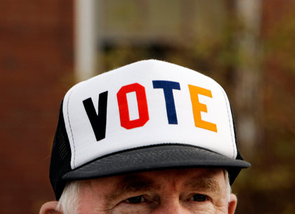 man wearing cap with VOTE on brim