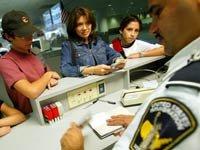 Un agente de inmigración sellando los pasaportes de una familia hispana - Lotería de visas