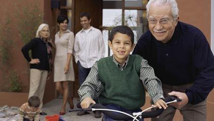 Abuelo ayudando a montar bicicleta a su nieto - Censo para los latinos