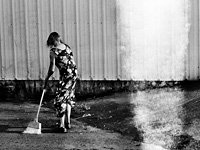 In bankrupt Vallejo, Calif., a woman sweeps an abandoned car dealership, her home.