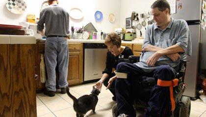 Persona en silla de ruedas y su familia en la cocina que se verian afectadas con los recortes del Medicaid