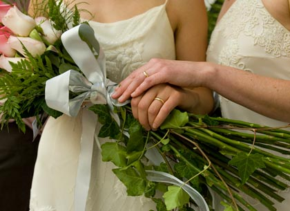 Two women hold hands after getting married at city hall in San Francisco, California.