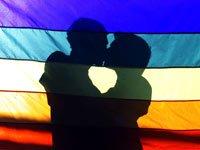 Dos hombres se abrazan detrás de una bandera con un arco íris, Derechos homosexuales