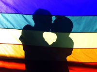 Two men embrace behind a rainbow flag, Same Sex Rights
