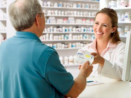 pharmacist handing man prescription