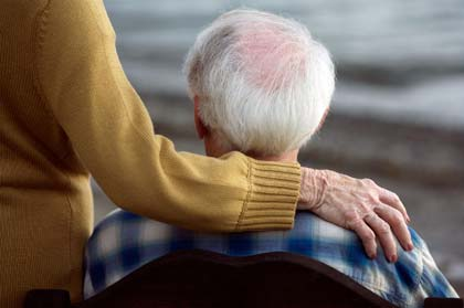 Senior couple, woman's hand on man's shoulder, rear view, close-up