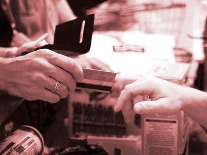 man handing his credit card