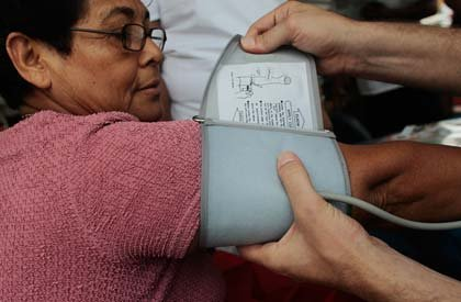 A nurse applies a blood-pressure cuff to a woman during a free health-screening clinic