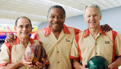 Men in team uniforms holding bowling balls
