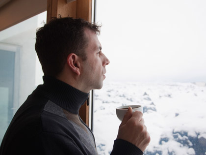 caucasian man with cup of coffee at window