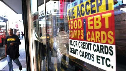 A sign in a market window advertises the acceptance of food stamps