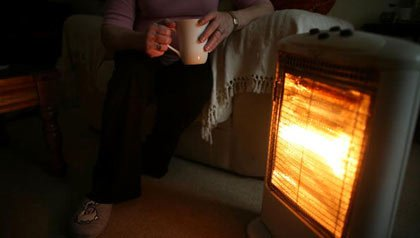 old age pensioner keeps warm with the aid of an electric heater